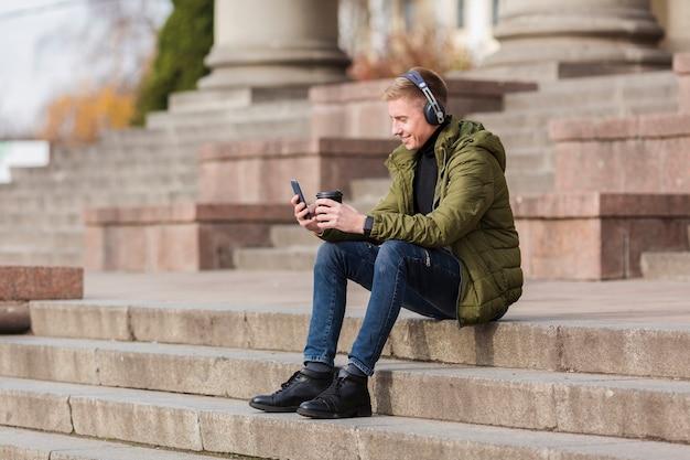 外のヘッドフォンで音楽を聴くロングショットの若い男