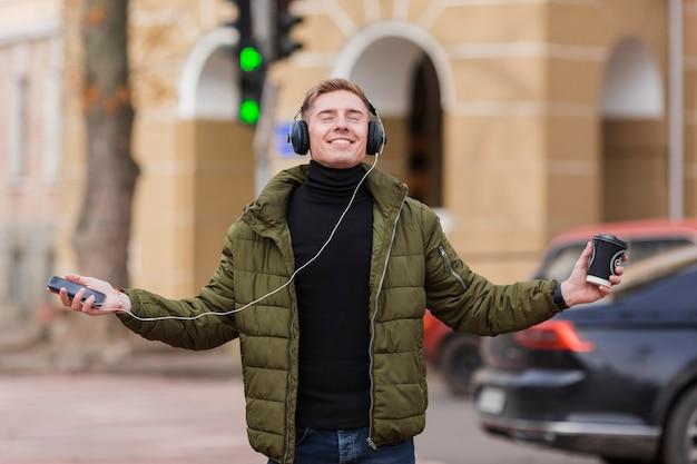 Улыбающийся молодой человек слушает музыку в наушниках на улице