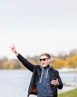 Человек слушает музыку на наушники на открытом воздухе с копией пространства