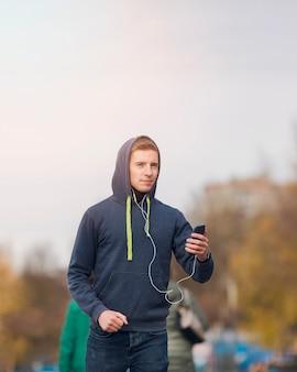 ジョギングしながらイヤホンで音楽を聴く若い男