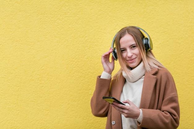 Современная женщина слушает музыку в наушниках с копией пространства