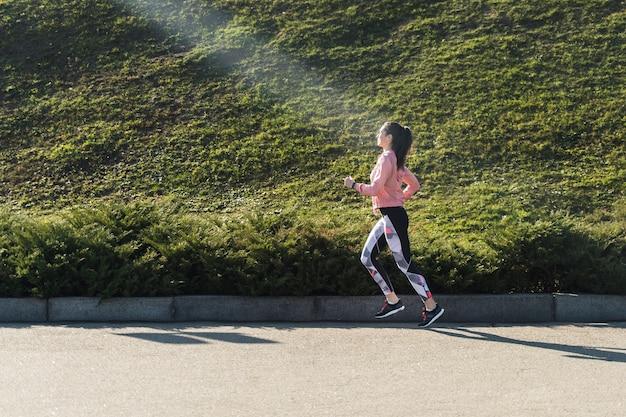屋外を実行しているフィットの若い女性