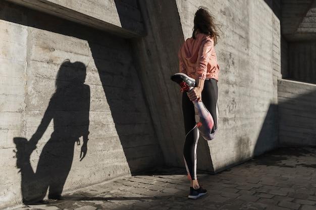 Вид сзади женщина растягивается перед бегом