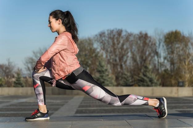 Подходит молодая женщина, растяжения на открытом воздухе