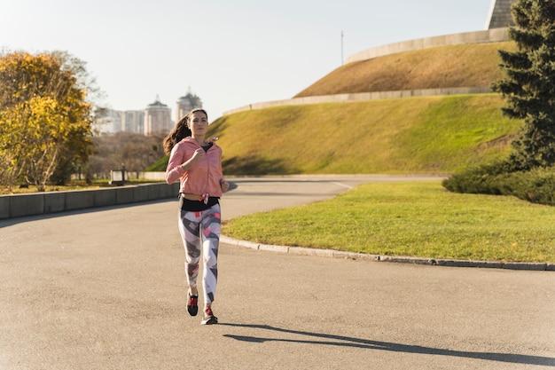 Активная молодая женщина работает в парке