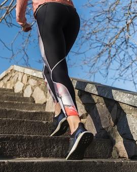 階段を走っているアクティブな女性