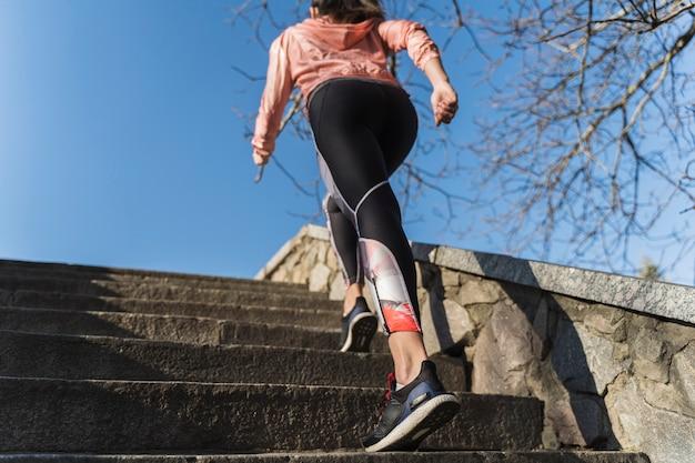 屋外階段を登る若い女性に合う