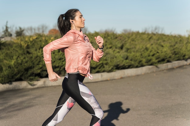Портрет подходящей женщины, бегающей трусцой в парке