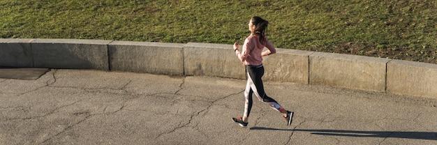 アクティブな若い女性が屋外ジョギング