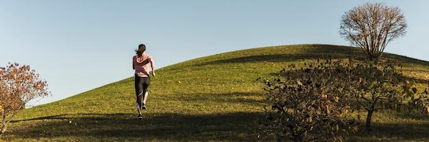 公園で走っているロングショット女性