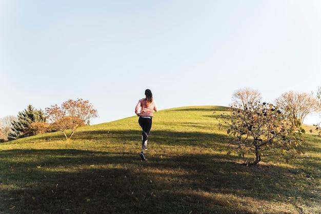 公園で走っているアクティブな若い女性