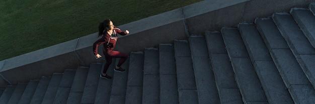 Подходит молодая женщина, поднимаясь по лестнице