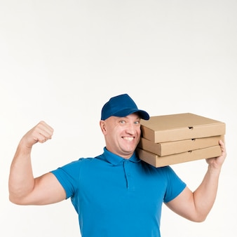 Улыбающийся курьер держит коробки для пиццы и показывает бицепс
