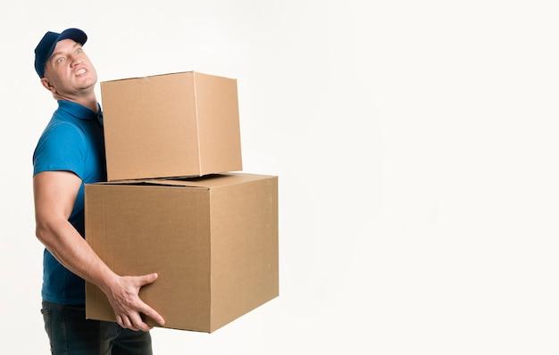 Вид сбоку доставщик держит тяжелые картонные коробки