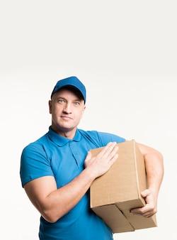 Доставка человек позирует, касаясь картонной коробке
