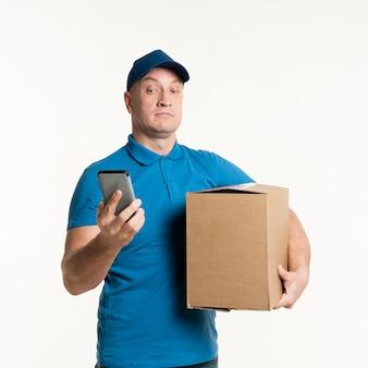 Доставка человек, глядя удивлен на телефон, держа картонную коробку