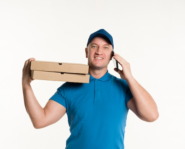 Счастливый доставщик несет коробки для пиццы и держит телефон
