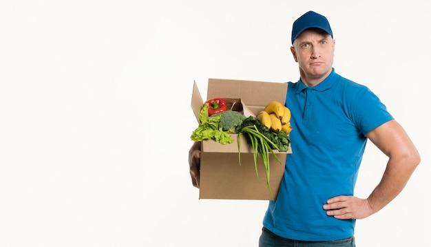 Доставка человек позирует смелый с продуктовой коробкой