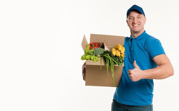 Доставка человек позирует с продуктовой коробке и пальцы вверх