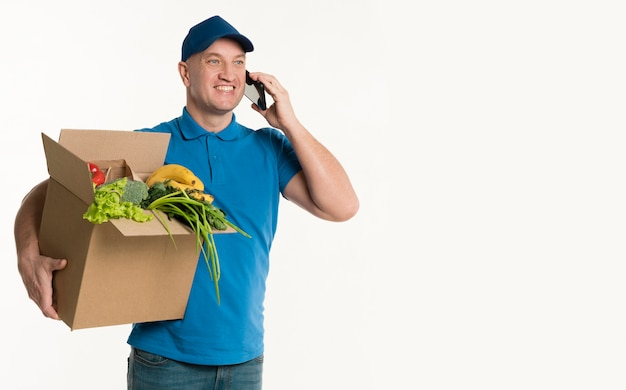 Счастливый доставщик разговаривает по телефону и держит коробку с продуктами