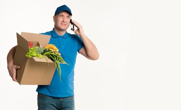 食料品の箱とコピースペースと電話で話している配達人