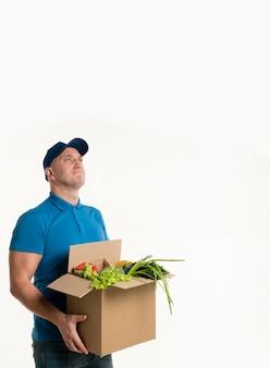 Задумчивый доставщик позирует с коробкой продуктов