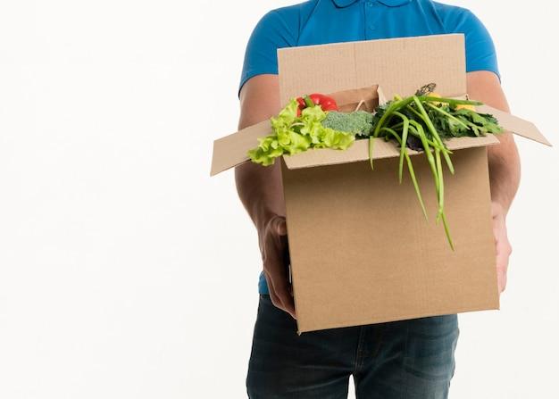 Вид спереди продуктовой коробки, проведенной доставщиком