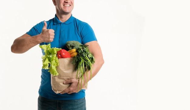 Вид спереди доставщик с продуктовый мешок и пальцы вверх
