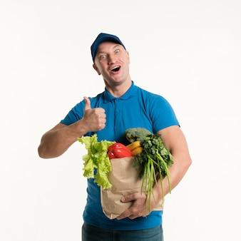 Доставка человек дает большие пальцы и держит продуктовый мешок