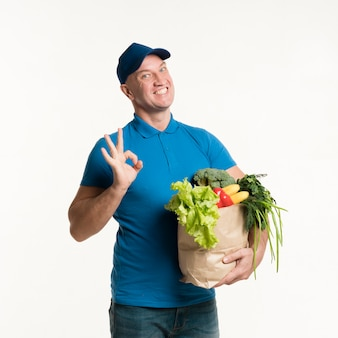 Счастливый доставщик держит продуктовый мешок