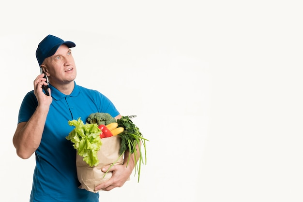 食料品の袋を手に電話で配達人