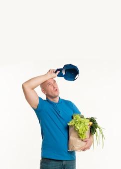 食料品の袋でポーズをとって疲れの配達人