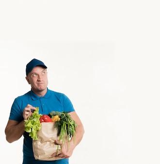 Доставка человек позирует с продуктовой сумкой
