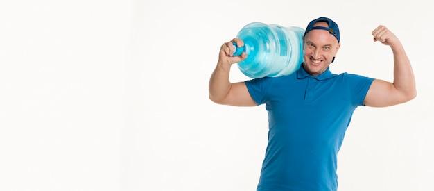 水のボトルを運ぶと力こぶを示す配達人