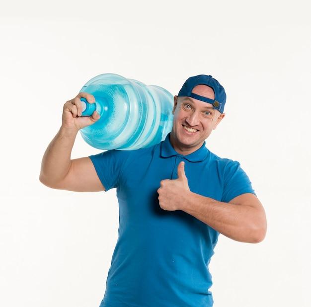 配達人が肩に水のボトルを運んでいる間親指を立てる
