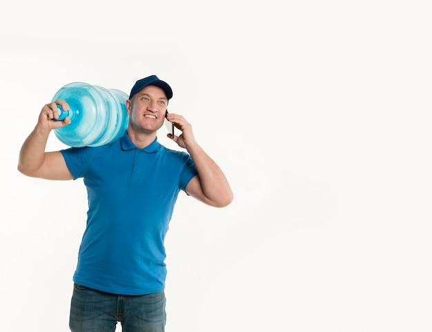 水のボトルとスマートフォンを運ぶスマイリー配達人の正面図
