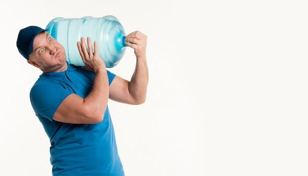 重い水のボトルを運ぶ配達人