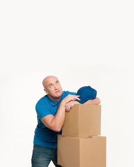 Усталый доставщик отдыхает на картонных коробках