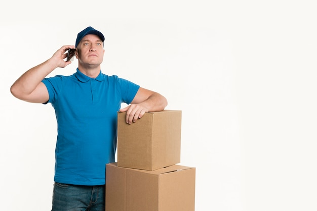 Доставка человек разговаривает по телефону и позирует с картонными коробками