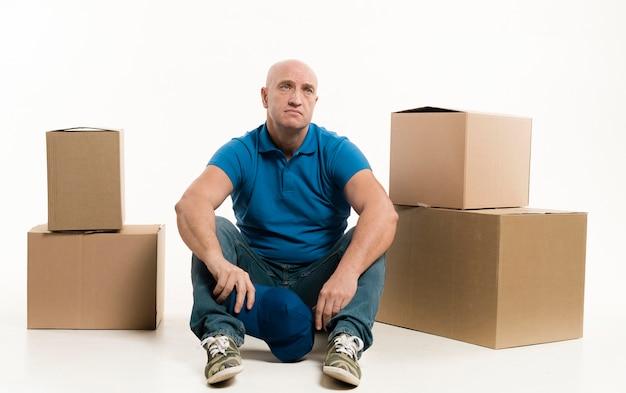 Усталый доставщик позирует с картонными коробками