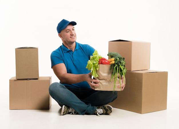 食料品の袋を押しながら笑みを浮かべて配達人