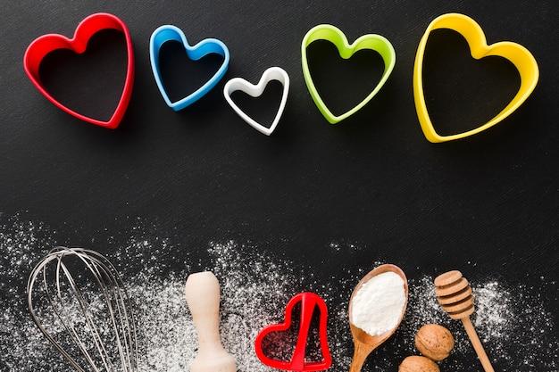 Вид сверху кухонной утвари с разноцветными сердечками и мукой