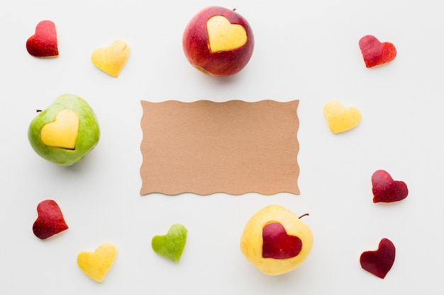 Вид сверху бумаги с яблоками и фруктами в форме сердца