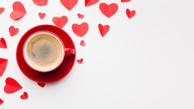 バレンタインデーのためのコーヒーと紙のハート形の平面図