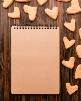 Вид сверху блокнот и печенье в форме сердца валентина