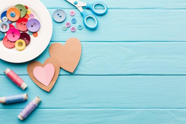 ミシン用品とバレンタインデーの紙の心のフラットレイアウト