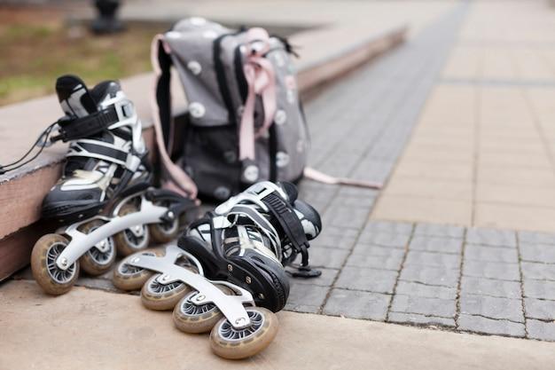 Расфокусированные ролики на асфальте с рюкзаком