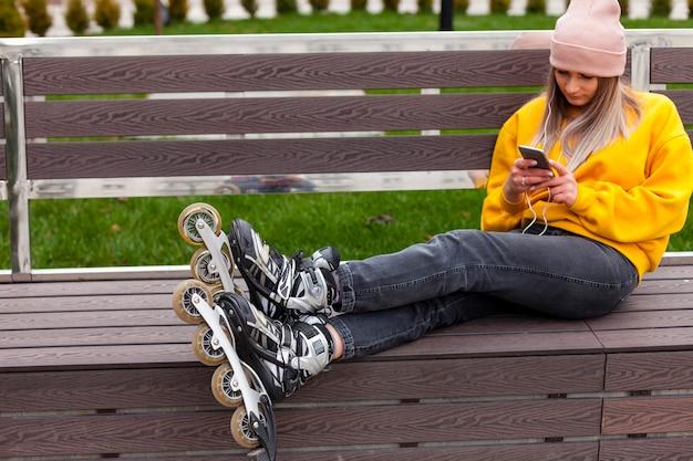 Женщина с роликами сидит на скамейке и смотрит на телефон