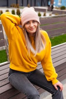 Женщина с шапочкой, улыбаясь и позирует