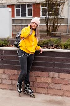 Женщина в роликовых коньках позирует с шапочкой и рюкзаком